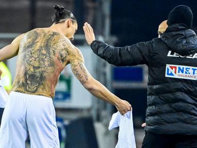 Striker AC Milan, Zlatan Ibrahimovic, menukar jersey saat melawan Cagliari pada laga Liga Italia di Sardegna Arena, Senin (19/1/2021). AC Milan menang dengan skor 2-0. (AFP/Alberto Pizzoli)