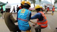Karyawan PT PLN (Persero) bergotong rotong mengangkat tiang yang akan digunakan untuk penyangga kabel listrik di Natuna, Kepulauan Riau. (Foto: Humas PLN)