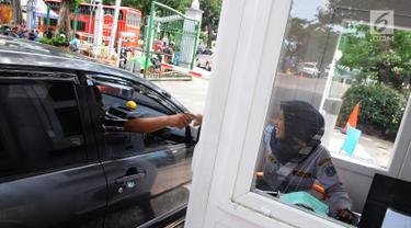 Pengendara mobil memberikan tiket parkir ke petugas di parkiran IRTI kawasan Monas, Jakarta, Jumat (11/1). Pemerintah DKI Jakarta mencabut insentif parkir kendaraan ASN atau PNS di IRTI Monas, Jakarta Pusat. (Liputan6.com/Herman Zakharia)