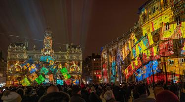 Orang-orang melihat balai kota Lyon (tengah) dan alun-alun Place des Terreaux yang diterangi cahaya lampu selama Festival of Lights (Fete des Lumieres) di kota Lyon, Prancis, Kamis (5/12/2019). Festival Cahaya ini merupakan salah satu kegiatan yang paling terkenal di Lyon. (ROMAIN LAFABREGUE / AFP)