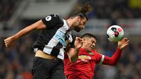 Striker Newcastle, Andy Caroll, duel udara dengan bek Manchester United, Marcos Rojo, pada laga Premier League di Stadion St James Park, Newcastle, Minggu (6/10). Newcastle menang 1-0 atas MU. (AFP/Paul Ellis)