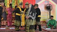 Bupati Bengkalis Amril Mukminin (dipakaikan selempang) ketika menerima gelar adat dari LAM Kabupaten Bengkalis. (Liputan6.com/Istimewa/M Syukur)