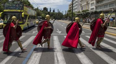 Sekelompok Pria berpakaian seperti tentara Yunani kuno menyeberang jalan sambil membawa tombak, perisai saat pertunjukan di Konstitusi (Syntagma) persegi di Athena, Yunani (21/6/2015). (REUTERS /Marko Djurica)