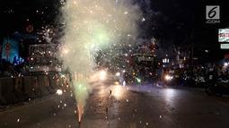 Warga menyalakan kembang api di tengah pawai untuk memeriahkan malam takbiran di sepanjang Jalan Mas Mansyur, Tanah Abang, Jakarta Pusat, Kamis (14/6) malam. (Liputan6.com/Johan Tallo)