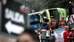Petugas pemadam kebakaran saat mengevakuasi bus usai kecelakaan di Lima, Peru, (9/10). Menurut petugas pemadam kebakaran, sedikitnya tujuh orang tewas setelah  bus wisata tersebut keluar jalur saat turun bukit di distrik Rimac. (AFP Photo/Andina/Ho)