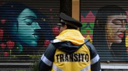 Polisi lalu lintas berdiri di depan toko yang dihiasi mural sebagai bagian dari program pemerintah di Mexico City, 30 Agustus 2017. Mural  sebagai bagian dari upaya pemerintah menghidupkan kembali ruang publik di wilayah kota tua. (ALFREDO ESTRELLA/AFP)