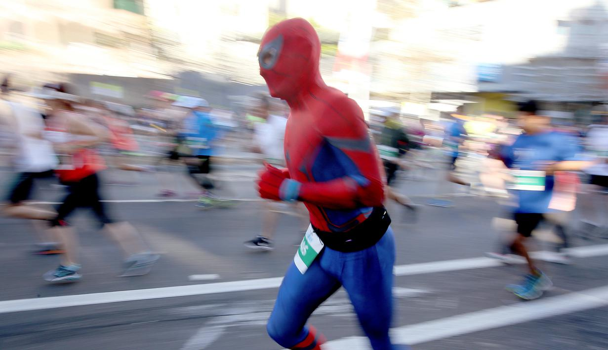 Salah satu peserta mengenakan kostum Spiderman saat berpartisipasi dalam lomba lari City2Surf Fun di Sydney, Australia, Minggu (13/8). Lomba ini merupakan acara lari santai tahunan dengan rute sepanjang 14 kilometer. (AP Photo/Rick Rycroft)