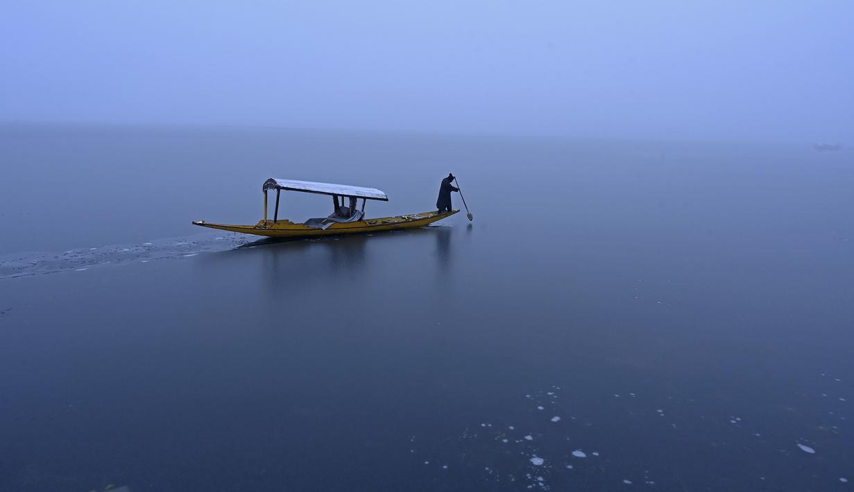 Seorang pria mengendarai perahu di dekat bagian beku danau Dal setelah hujan salju lebat di Srinagar (16/1/2020). Banyak daerah terpencil di lembah telah terputus akibat hujan salju lebat tersebut. (AFP Photo/Tauseef Mustafa)