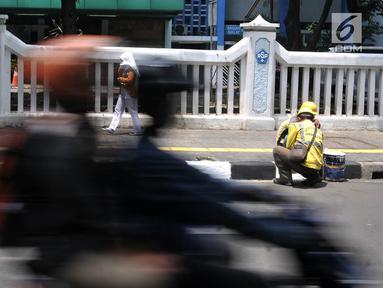 Petugas Suku Dinas Bina Marga Jakarta Timur saat menyelesaikan pengecatan trotoar di Jalan Persahabatan Raya, Jakarta, Rabu (27/3). Kegiatan pengecatan ini rutin dilakukan guna merawat sekaligus mempercantik jalur pedestrian tersebut. (merdeka.com/Iqbal S. Nugroho)