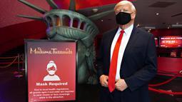Sosok Donald Trump yang bermasker berdiri di dekat tanda bertuliskan Mask Required' saat Madame Tussauds New York dibuka kembali di New York City, Kamis (27/8/2020). Patung lilin Donald Trump dengan mengenakan masker akan menyambut pengunjung dipintu masuk museum. (Cindy Ord/Getty Images/AFP)