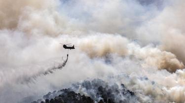 Sebuah helikopter militer menjatuhkan air di atas hutan dekat Desa Schinos, Korintus, Yunani, Kamis (20/5/2021). Kebakaran hutan besar di sebelah barat Athena merusak rumah-rumah dan mendorong evakuasi. (AP Photo/Petros Giannakouris)