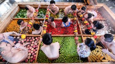 Pengunjung menikmati berendam di kolam air panas berbentuk hot pot di sebuah hotel di Hangzhou, China, Minggu (27/1). Pemandian air panas itu dirancang untuk mempromosikan gaya hidup sehat menjelang Tahun Baru Imlek pada 5 Februari mendatang. (STR/AFP)