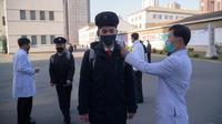 Mahasiswa menjalani pemeriksaan suhu sebagai upaya mencegah penyebaran pandemi Covid-19 di Universitas Kedokteran Pyongyang di Pyongyang, Rabu (22/4/2020). Korea Utara memberlakukan pembatasan ketat guna mengantisipasi penyebaran pandemi yang telah menyebar hampir di seluruh dunia. (KIM Won Jin/AFP)
