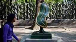 """Seorang pria melihat patung """" Dance of Time I """" saat pameran """"Salvador Dali: Urban Dreams"""" di Mexico City, Selasa (14/3). Patung-patung tersebut adalah karya seniman asal spanyol yang bernama Salvador Dali. (AFP PHOTO / RONALDO SCHEMIDT)"""