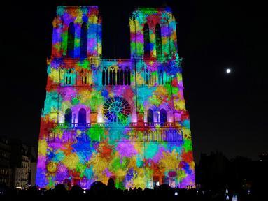 """Sebuah foto pada 20 Oktober 2018 menunjukkan Gereja Katedral Notre Dame selama pertunjukan cahaya berjudul """"Dame de Coeur"""" di Paris, Prancis. Pertunjukan cahaya tersebut bagian dari perayaan seratus tahun Perang Dunia I. (Photo by Ludovic MARIN/AFP)"""