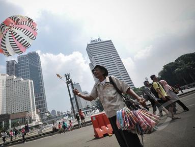 Pedagang parasut mainan saat menerbangkan barang dagangannya di kawasan Bundaran HI, Jakarta, Minggu (22/3/2015).  Seiring dengan perkembangan zaman dan modernisasi, permainan tradisional kini mulai tergantikan. (Liputan6.com/Faizal Fanani)
