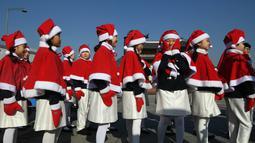 Anak-anak Korea Selatan mengenakan pakaian Santa Claus berjalan di depan Istana Gyeongbokgung, Seoul, Jumat (30/11). The Salvation Army meluncurkan kampanye amal akhir tahun untuk orang miskin. (Jung Yeon-je/AFP)