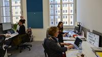 Sejumlah karyawan berada di meja kerja mereka pada hari pembukaan kantor baru raksasa mesin pencari internet, Google, di Berlin, Selasa (22/1). Google kembali membuka kantor cabang yang baru di ibu kota Jerman tersebut. (Photo by Tobias SCHWARZ / AFP)