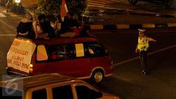 Petugas kepolisian memberhentikan sebuah mini bus di kawasan Matraman, Jakarta Timur, Jum'at (17/7/15) malam. Mini Bus tersebut melanggar peraturan karena menaikan penumpang diatap saat perayaan malam takbiran.(Liputan6.com/Faisal R Syam)