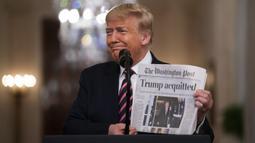"""Presiden Donald Trump tersenyum saat menunjukkan surat kabar dengan tajuk utama bertuliskan """"Trump dibebaskan"""" di Ruang Timur Gedung Putih, Washington (6/2/2020). Para senator AS memutuskan bahwa Trump tidak bersalah dalam sidang pemakzulan. (AP Photo/Evan Vucci)"""