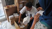 Petugas memeriksa kemasan kardus telepon seluler ilegal di gudang distributor, di ruko kawasan Cempaka Mas, Jakarta, Senin(15/6/2015). Penggeledahan tersebut terkait beberapa laporan dari masyarakat. (Liputan6.com/Herman Zakharia)