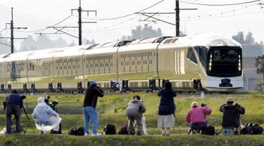 """Fotografer mengambil gambar kereta api mewah """"Train Suite Shiki-Shima"""" yang melintas di Nikko, timur laut Tokyo, Jepang, 1 Mei 2017. Kereta yang pertama kalinya beroperasi pada 1 Mei ini melayani rute Tokyo-Hokkaido. (Yoshitaka Sugawara/Kyodo News via AP)"""