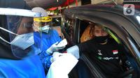 Paramedis menyuntikkan vaksin COVID-19 secara drive thru kepada pengendara mobil di GOR Pajajaran, Kota Bogor, Jawa Barat, Rabu (17/3/2021). Kegiatan ini menargetkan 600 warga per hari dan berlangsung hingga tiga bulan ke depan. (merdeka.com/Arie Basuki)
