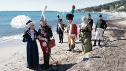 Orang-orang yang mengenakan kostum era Napoleon Bonaparte berjalan di pantai dalam rangka peringatan 200 tahun kematian Napoleon Bonaparte di Saint-Helene, Golfe-Juan, Prancis, 16 Maret 2021. Kaisar Napoleon Bonaparte hidup pada 15 Agustus 1769 hingga 5 Mei 1821. (Valery HACHE/AFP)