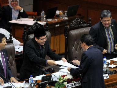 Ketua Badan Anggaran DPR Ahmadi Noor Supit memberikan laporan pandangan fraksi terhadap RAPBN 2016 kepada Ketua Rapat Taufik Kurniawan (kedua kiri) saat Rapat Paripurna Ke-9 di Kompleks Parlemen, Jakarta, Jumat (30/10/2015). (Liputan6.com/JohanTallo)