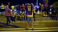 Pendukung FC Barcelona mendatangi Camp Nou dan berkumpul di depan markas klub, setelah mendengar kabar Lionel Messi yang akan hengkang, di Barcelona, Selasa (25/8/2020). Mereka melakukan protes meminta Presiden Barcelona, Josep Maria Bartomeu, berhenti dari jabatannya. (Pau BARRENA/AFP)