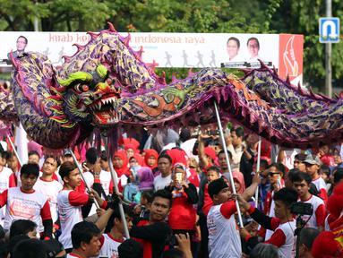 Peserta memainkan kesenian tradisional liong saat Kirab Kebangsaan Indonesia Raya di Cibinong, Kab Bogor, Minggu (14/5). Kirab diikuti puluhan organisasi kepemudaan se Kabupaten Bogor. (Liputan6.com/Helmi Fithriansyah)