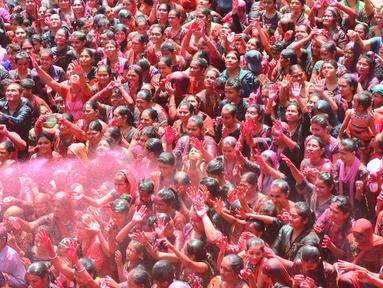 Umat Hindu India disemprot dengan cairan berwarna dalam festival keagamaan Holi di Kuil Swupramayan Kalupur, Ahmedabad, Rabu (20/3). Holi merupakan festival Hindu terbesar di India yang menandai dimulainya musim semi. (SAM PANTHAKY / AFP)