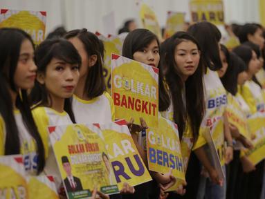 Sejumlah gadis muda cantik membawa poster saat penutupan Musyawarah Nasional Luar Biasa (Munaslub) partai Golkar di Jakarta, Rabu (20/12). (Liputan6.com/Faizal Fanani)