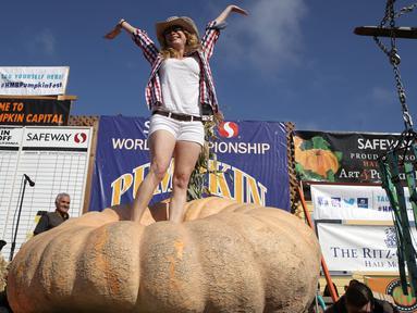 Cindy Tobeck berdiri di atas labu seberat 1.736 pon miliknya dalam lomba Safeway World Championship Pumpkin Weigh-Off di Half Moon Bay, California, Amerika Serikat, Senin (14/10/2019). Seorang petani keluar sebagai juara dengan labu seberat 2.175 pon miliknya. (Justin Sullivan/Getty Images/AFP)
