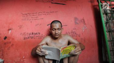 Santri beristirahat sambil membaca buku agama dalam ruangan berjeruji di Pesantren Rehabilitasi Narkoba Hikmah Syahadah, Pasir Nangka, Tigaraksa, Tangerang, Rabu (4/9/2019). Sekitar 50 santri yang umumnya mantan pecandu narkoba menjalani terapi penyembuhan di pesantren ini. (merdeka.com/Arie Basuki)