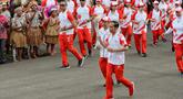 Presiden Joko Widodo didampingi Menpora Imam Nahrawi membawa api obor Asian Games 2018 sebelum upacara penurunan Bendera Merah Putih di Istana Negara Jakarta, Jumat (17/8). (Liputan6.com/Pool/Eko)