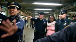 Petugas NYPD menangkap seorang perempuan tersangka pelaku pendorongan di stasiun Time Square, New York, Senin (7/11). Tersangka mendorong seorang perempuan hingga tewas ke jalur subway (kereta bawah tanah) . (REUTERS/James Carman)