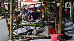 Pedagang ikan bandeng melayani pembeli di kawasan Rawa Belong, Jakarta Barat, Rabu (10/2/2021). Para pedagang ikan bandeng berdagang di pinggir jalan dan menjajakan kapada setiap pengendara yang melintas. (Liputan6.com/Johan Tallo)