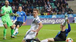 Bek Jerman, Marcel Halstenberg, berebut bola dengan bek Estonia, Joonas Tamm, pada laga Kualifikasi Piala Eropa 2020 di Talinn, Minggu (13/10). Estonia kalah 0-3 dari Jerman. (AFP/Janek Skarzynski)