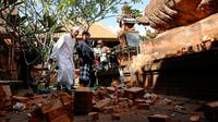 Pemuka agama dan prajurit TNI memantau kerusakan pada bagian candi yang runtuh akibat gempa di Pura Lokanatha, Denpasar, Bali, Selasa (16/7/2019). Gempa Magnitudo 5,8  yang mengguncang Bali dilaporkan terasa hingga ke Lombok dan wilayah Jawa Timur. (AP/Firdia Lisnawati)
