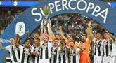 Pemain Juventus, Giorgio Chiellini mengangkat trofi Piala Super Italia 2018 seusai mengalahkan AC Milan pada laga final di King Abdullah Sports City, Kamis (17/1). Juventus keluar sebagai kampiun dengan meraih kemenangan tipis 1-0. (AP Photo)