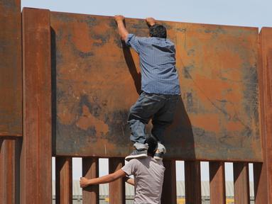 Seorang pemuda dibantu temannya memanjat tembok besi perbatasan antara Meksiko dan Amerika Serikat di negara bagian Chihuahua, Meksiko (6/4). Mereka menyeberang secara ilegal ke Sunland Park dari Ciudad Juarez. (AFP/Herika Matinez)
