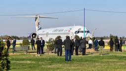 Petugas dan warga melihat kondisi pesawat Caspian usai tergelincir hingga berhenti di tengah jalan raya di Kota Bandar-e Mahshahr, Iran (27/1/2020). Dalam kejadian tersebut seluruh penumpang beserta kru selamat. (MOSTAFA GHOLAMNEZAD / ISNA / AFP)