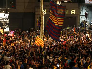 Pendukung Barcelona merayakan keberhasilan tim favorit mereka menjuarai La Liga Spanyol di Barcelona, Spanyol (18/5/2015). Barcelona juara setelah mengalahkan Atletico Madrid 1-0. (REUTERS/Gustau Nacarino)