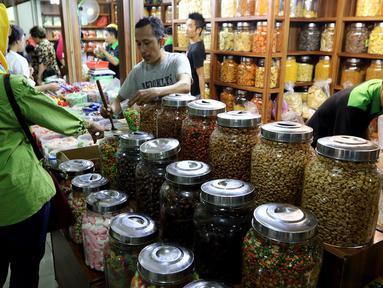 Pedagang melayani pembeli kue kering di Pasar Mayestik, Jakarta Selatan, Senin (11/6). Separuh Ramadan dan jelang lebaran masyarakat mulai berburu kue kering. (Liputan6.com/Johan Tallo)