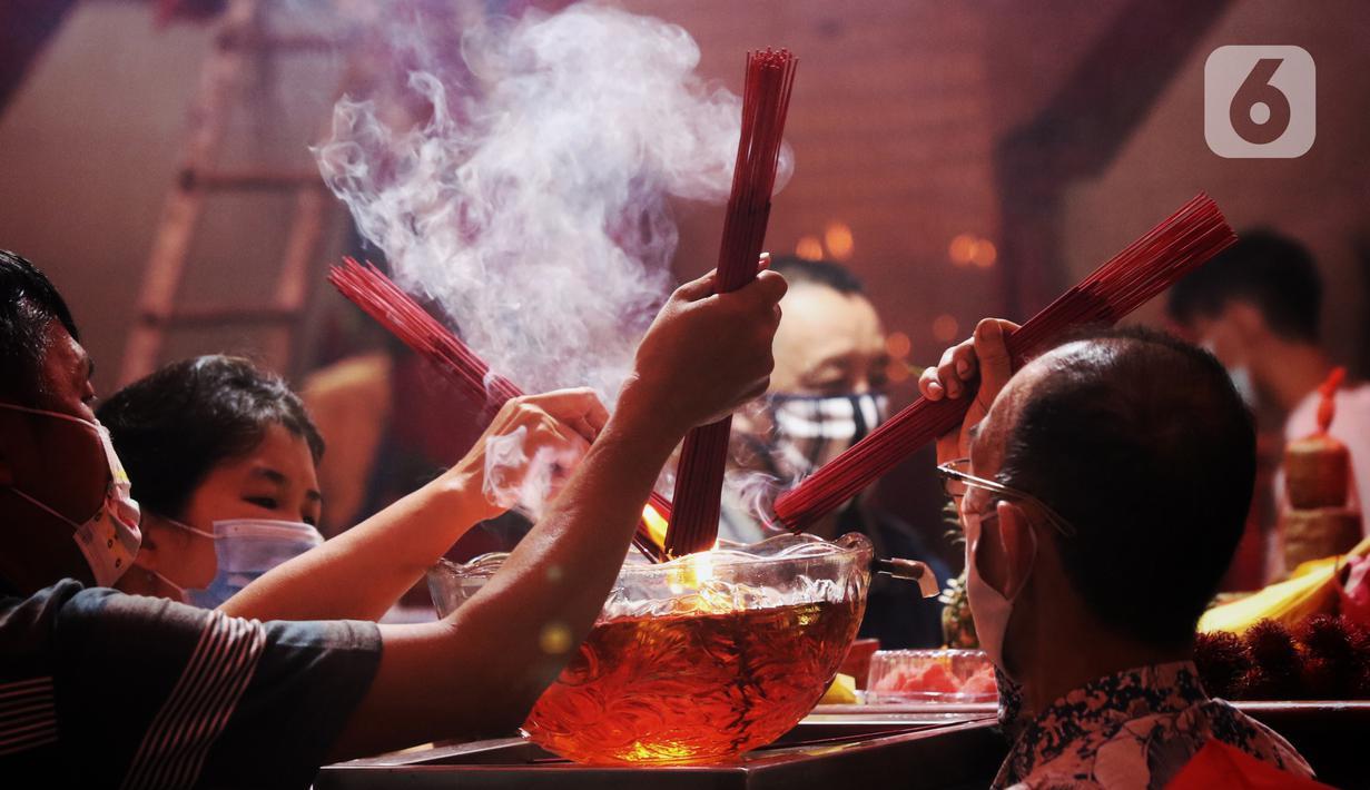 Warga keturunan Tionghoa menyalakan hio saat sembahyang malam Imlek di Klenteng Boen San Bio, Tangerang, Kamis (11/2/2021). Meskipun di tengah pandemi Covid 19, sembahyang Imlek 2572 dilakukan dengan protokol kesehatan yang ketat dan membatasi jumlah warga yang sembahyang (Liputan6.com/Angga Yuniar)