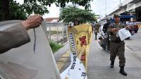 Petugas Satpol PP menertibkan Alat Peraga Kampanye (APK) di sepanjang Jalan Yos Sudarso, Jakarta Utara, Rabu (13/3). APK yang dipasang di sembarang tempat dan fasilitas umum melanggar SK KPU nomor 175. (merdeka.com/Iqbal S. Nugroho)