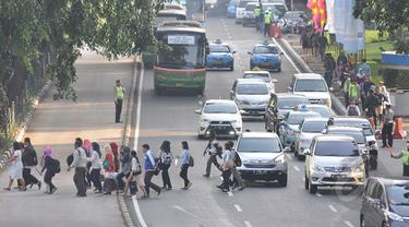 Sejumlah pekerja menyebrang jalan di kawasan Sudirman, Jakarta, Rabu, (22/4/2015). Adanya pengalihan arus untuk KAA membuat mereka terpaksa jalan kaki. (Liputan6.com/Johan Tallo)