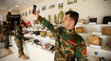 Seorang militer Kurdi Peshmerga berswafoto di sebelah bahan peledak dan barang-barang yang digunakan oleh militan Negara Islam (ISIS) di sebuah museum di Erbil, Irak, 12 Mei 2019. 'Museum ISIS' tersebut dibuka oleh militer Peshmerga. (REUTERS/Azad Lashkari)