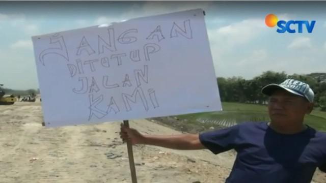 Warga juga membawa poster kertas bertuliskan ungkapan protes atas ditutupnya akses jalan kampung mereka yang membentang utara ke selatan